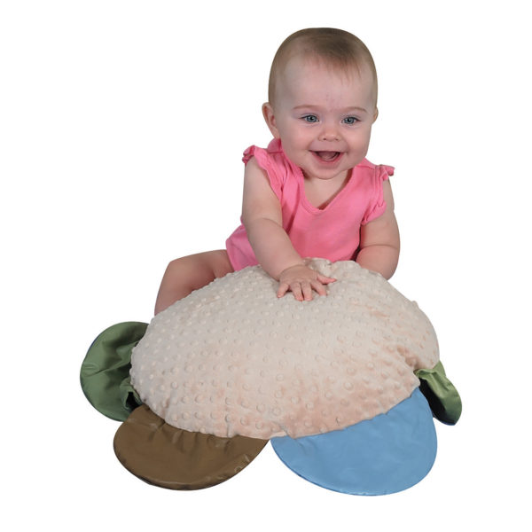 baby playing with flower pillow